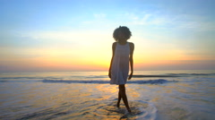 Silhouette of African American girl dancing on beach on vacation at sunset Stock Footage