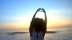 Young ethnic girl making hands heart symbol with hands on beach at sunrise Stock Footage