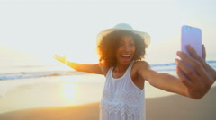 Attractive African American woman taking selfie on mobile on ocean beach Stock Footage