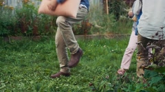 Happy kids fight pillows in yard of country house. Childhood. Man play balalaika Stock Footage
