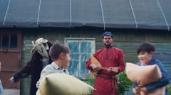 Two boys and girl fight pillows in country house. Childhood. Man play balalaika Stock Footage