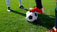 Soccer ball on center point of football field, two players starting the match Stock Footage