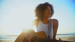 Portrait of African American girl playing the guitar and singing on beach Stock Footage