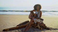 Beautiful African American woman playing the guitar and singing on holiday beach Stock Footage