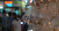 Young blond woman take a picture of gold aquarium fishes packed in plastic bag Stock Footage