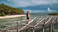 Young woman walking on boardwalk in ocean close to tropical island Stock Footage