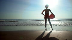Silhouette of African American woman playing on holiday beach with red ball Stock Footage