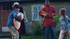Kids fight pillows in yard of country house. Feathers. Men play balalaika. Happy Stock Footage
