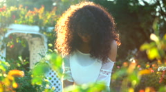 Happy young African American woman enjoying the park flowers Stock Footage