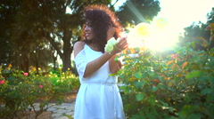 Beautiful African American female enjoying the garden flowers Stock Footage