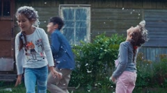 Kids and man throw feathers from pillows in yard of country house. Summer Stock Footage