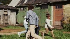 Children run around girl with tied sleeves on back in yard of country house Stock Footage