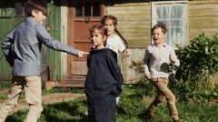 Kids run around girl with tied sleeves in yard of country house. Summer holiday Stock Footage