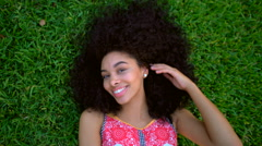 Portrait of young African American female with afro hair relaxing in the garden Stock Footage