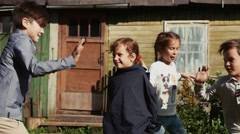 Children run around girl with tied sleeves in yard of country house. Shake hands Stock Footage