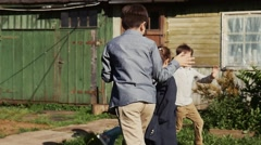 Children running around girl with tied sleeves in yard of country house. Summer Stock Footage