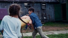 Kids fight pillows in yard of country house. Countryside. Entertainment. Summer Stock Footage