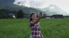 Woman takes selfie on amazing summer scenery Stock Footage