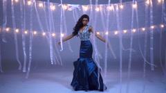 Portrait of slim ethnic girl model being filmed in beautiful gown in studio Stock Footage