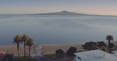 Aerial of palm trees on beach and Rangitoto island, auckland Stock Footage