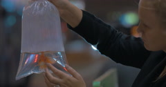 Woman holds in hand plastic package with aquarium gold fish in the shopping mall Stock Footage