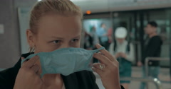Young blond woman wearing surgical mask in the entrance of clinic. Hong Kong Stock Footage