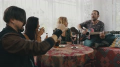 Friends relax in country house at table drink alcohol. Man playing guitar. Fun Stock Footage