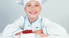 Young baker decorating meringue cake using chocolate and smiling at camera Stock Footage