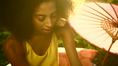 Attractive ethnic woman relaxing on Summer holiday in park sunset Stock Footage