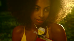 Attractive ethnic female listening music on Summer holiday in park sunset Stock Footage