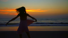 Silhouette of Caucasian American female dancing on beach on holiday at sunrise Stock Footage