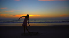 Silhouette of happy Caucasian American woman enjoying sunrise on ocean beach Stock Footage