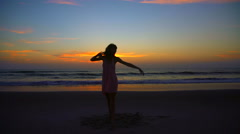 Silhouette of slim Caucasian American girl dancing on holiday beach at sunrise Stock Footage