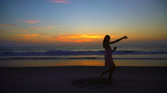 Silhouette of Caucasian American woman posing on beach on holiday at sunset Stock Footage