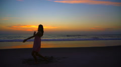 Silhouette of Caucasian American woman dancing on beach on vacation at sunset Stock Footage
