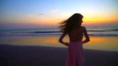 Silhouette of slim Caucasian American female dancing on holiday beach at sunset Stock Footage