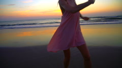Silhouette of Caucasian American female posing on beach on holiday at sunset Stock Footage