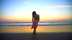 Silhouette of Caucasian American woman posing on beach on vacation at sunset Stock Footage