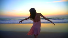 Cute Caucasian American girl enjoying holiday beach at sunset in silhouette Stock Footage