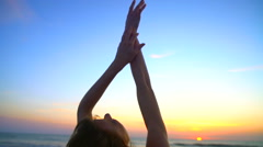 Silhouette of slim Caucasian American female posing on vacation beach at sunset Stock Footage