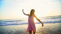 Young Caucasian American woman dancing on beach on vacation at sunrise Stock Footage