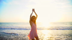 Young Caucasian American woman dancing on beach on holiday at sunrise Stock Footage