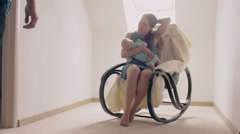 Mother smiling at newborn son lulling him in a rocking chair. father comes to Stock Footage