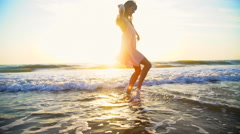 Young Caucasian American woman enjoying vacation beach at sunrise Stock Footage