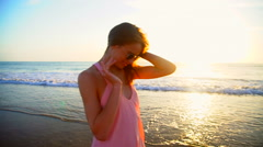 Portrait of cute Caucasian American woman enjoying holiday beach at sunrise Stock Footage