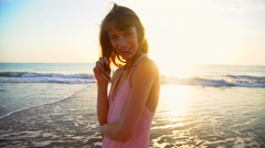 Portrait of Caucasian American woman posing on beach on holiday at sunrise Stock Footage