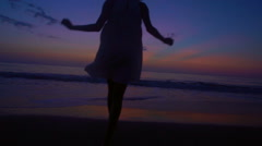Silhouette of African American girl dancing on beach on vacation at sunrise Stock Footage