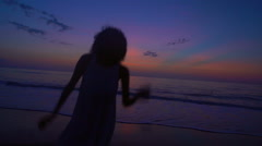 Cute ethnic woman enjoying vacation beach at sunset in silhouette Stock Footage