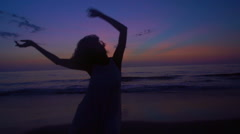 Silhouette of African American girl dancing on beach on holiday at sunrise Stock Footage