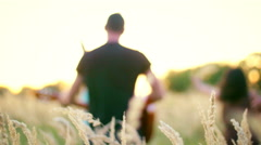 Beautiful girls and boys walking in the field - spikes in the sunset Stock Footage